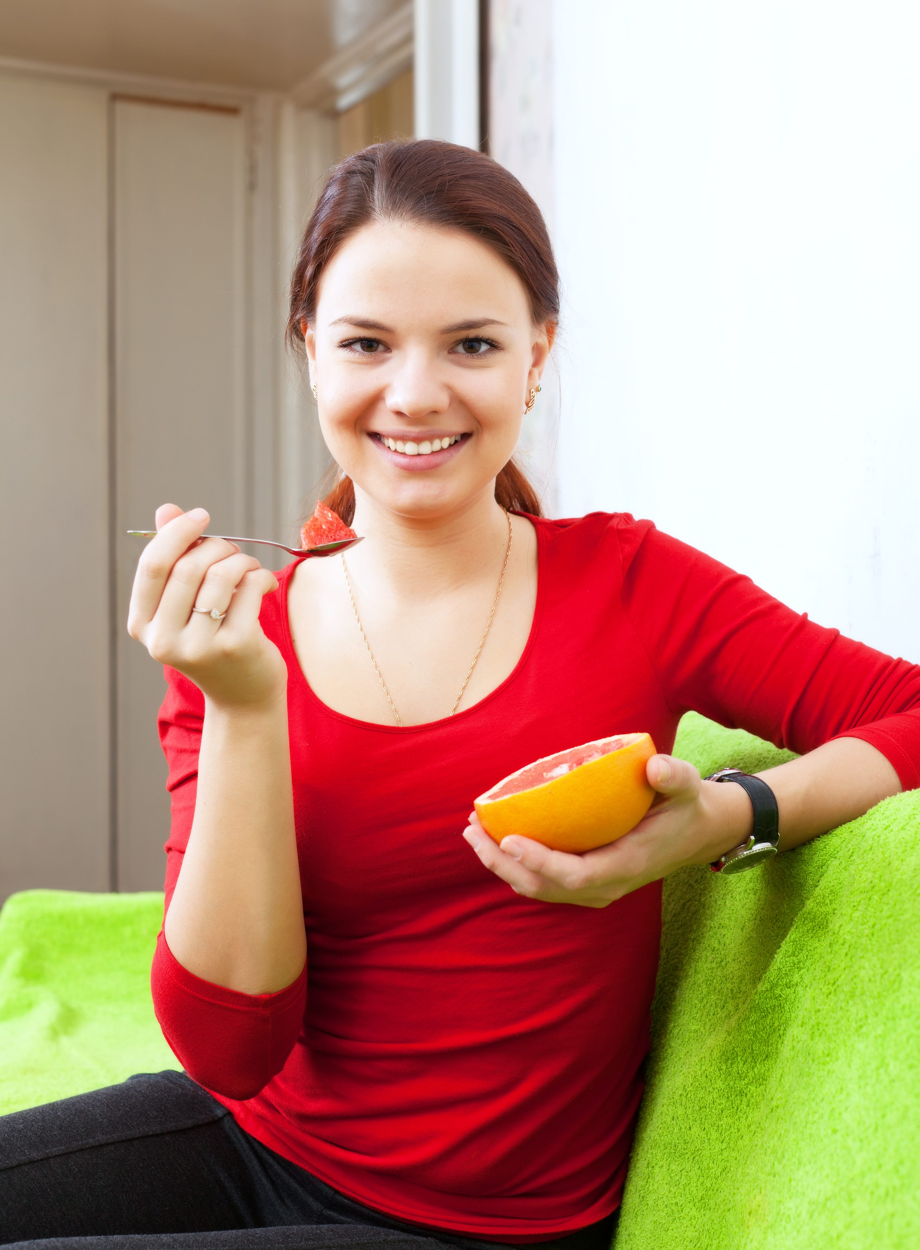 Portrait of long-haired girl in red eats grapefruit at home interior